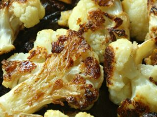 Roasted Cauliflower with caramelized onions and garlic. Topped and baked in Parmesan cheese for a delicious flavor. Perfect side dish for steak.