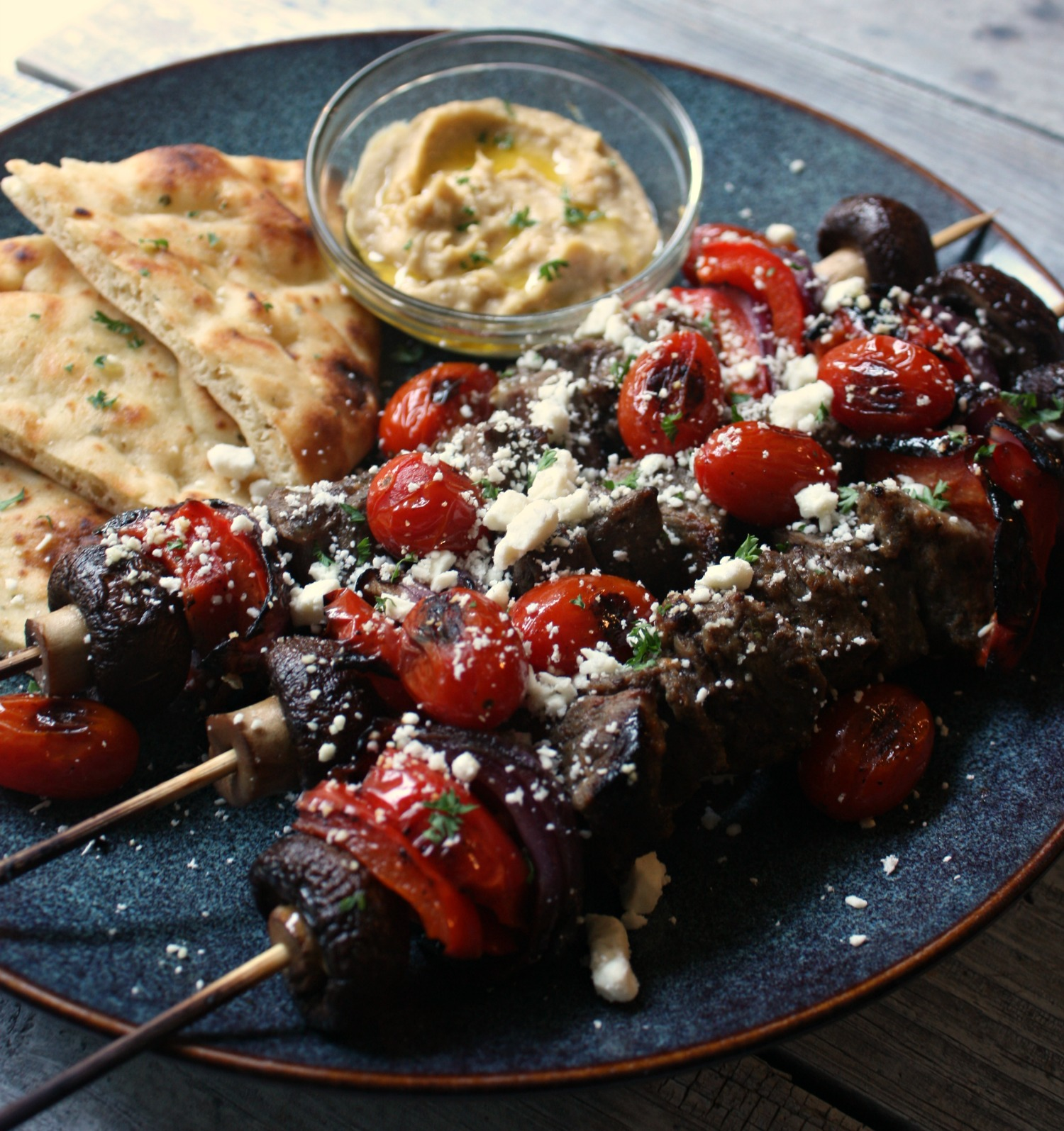 Beef Kabobs with Blistered Tomatoes and Feta Cheese. Served with grilled naan bread and a side of hummus.