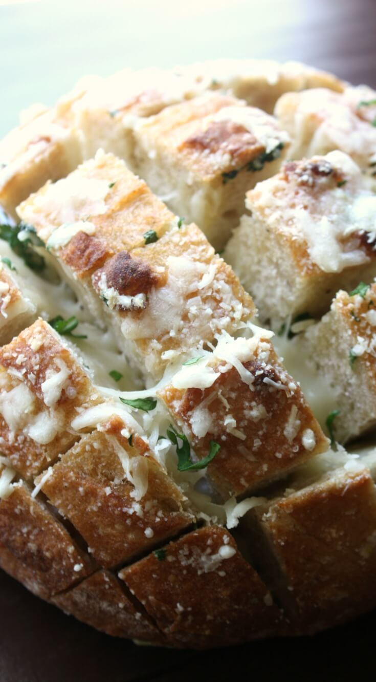 Cheesy Garlic Pull Apart Bread. Take a sourdough loaf and slice it, stuff it with butter, garlic and cheeses then bake until golden gooey goodness. My Cheesy Garlic Pull Apart Bread recipe is a great appetizer to share and have a few beers with.