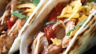 This Slow Cooker Chicken Tacos recipe is full of tender shredded chicken, peppers, and onions all slow cooked in salsa for a flavorful easy dinner.